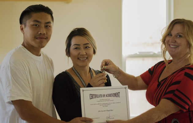 Desiree Gonzalez of CHIP (R) hands keys to new homeowners Chad Her and Zer Lee. (Photo by Tehama Group Communications)