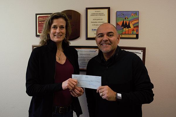 CHIP's Interim CEO Kris Zappettini presents a $7200 check to  Guillermo Sandoval  for Tri Counties Bank's  Camp Fire Fund.