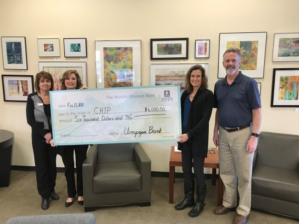 representatives from Umpqua Bank and CHIP holding a giant check