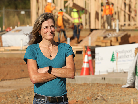 Kris Zappettini smiles for the camera as she stands in front of the active construction site at Paradise Community Village.